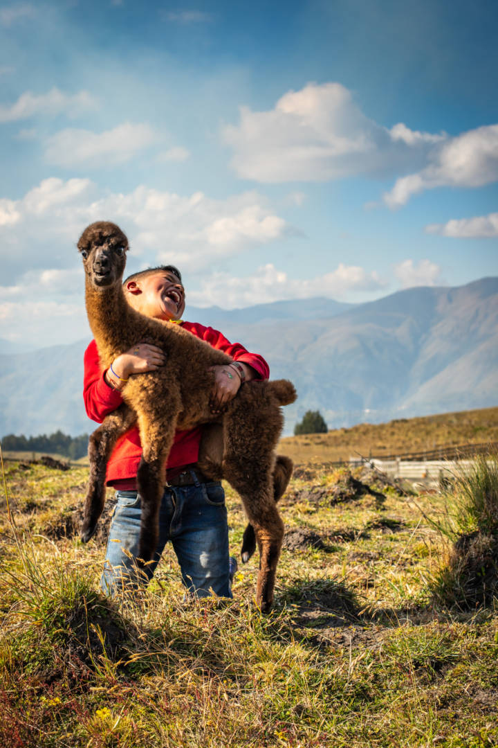 In Ecuador, 11-year-old Andy plays with an alpaca.