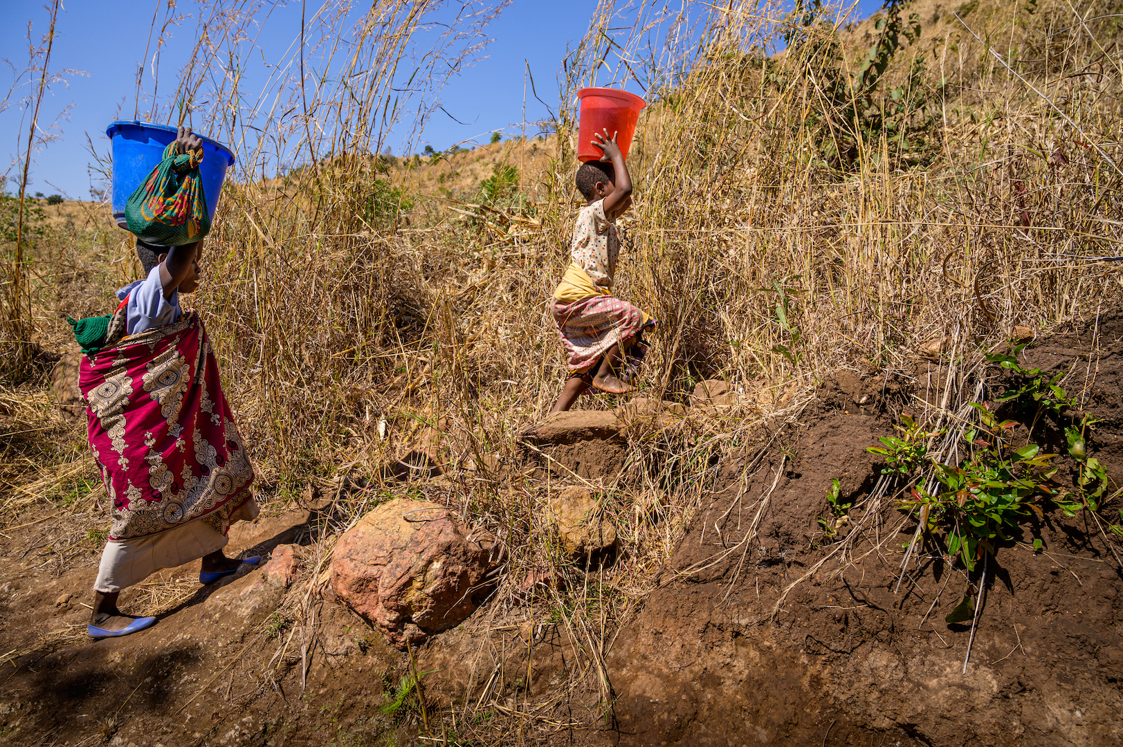Mother and daughter in Malawi make difficult trek to gather water.