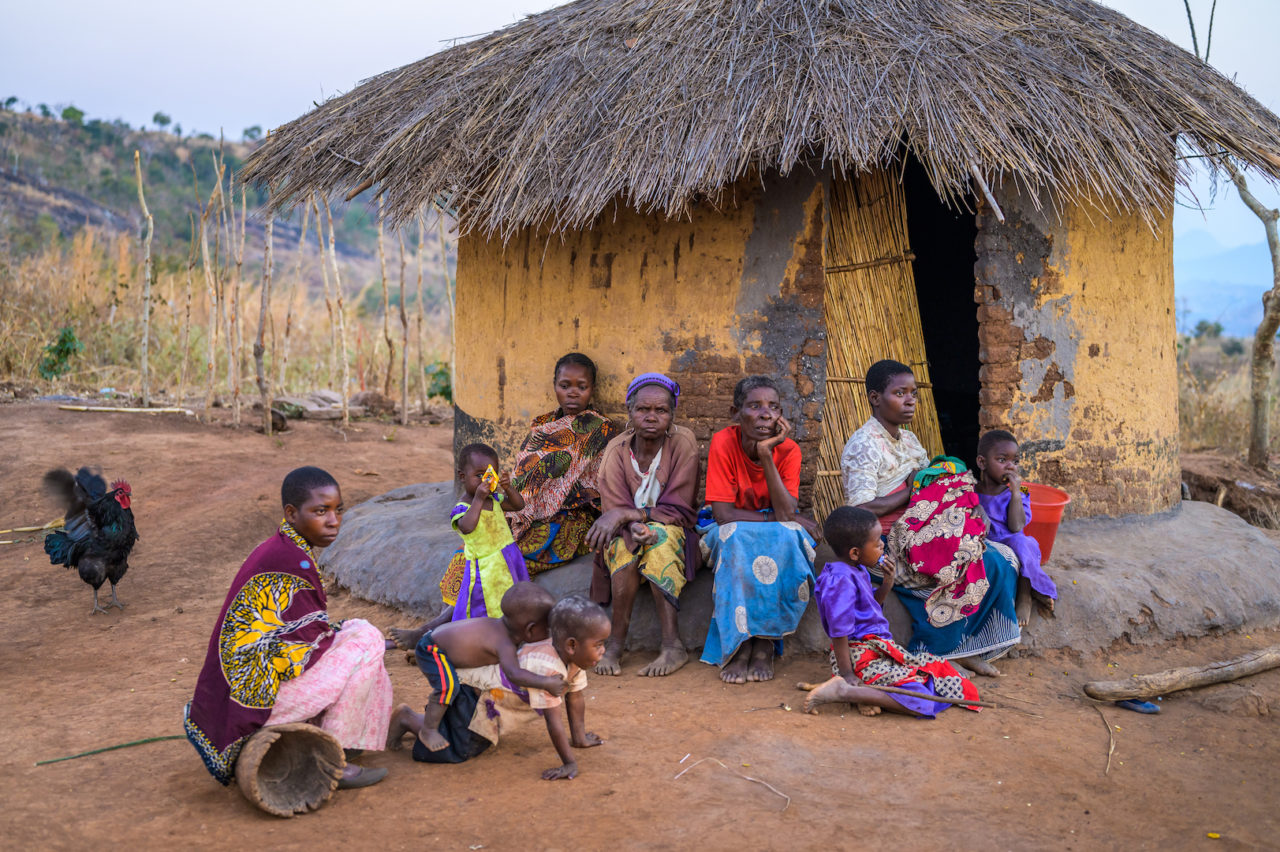 Eight-year-old Ireen's family sits outside their hut in Malawi.