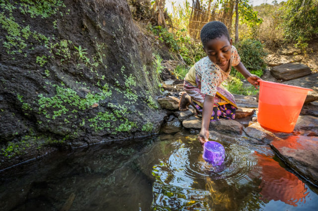 Eight-year-old Ireen dips her cup into a pool in Malawi.