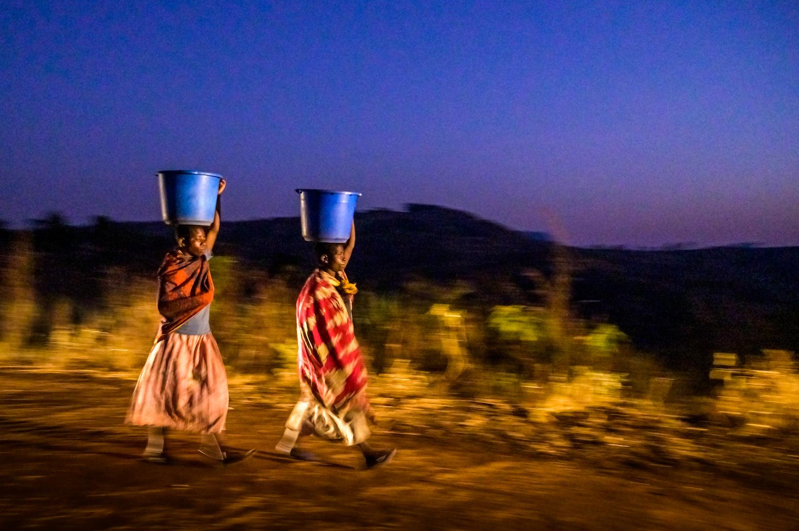 Twin sisters walk in the dark to gather water in Malawi.