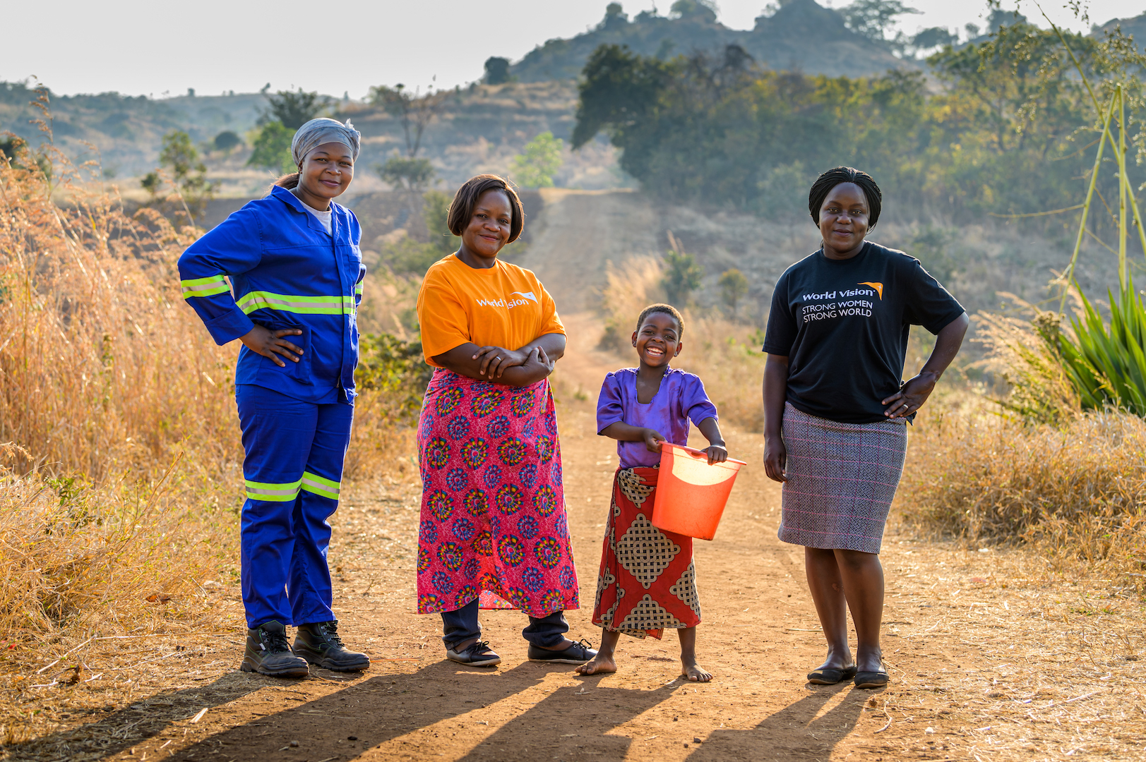 World Vision staff stand next to Ireen in Malawi.