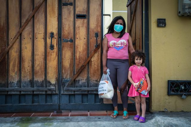 Woman wearing mask standing next to small child.