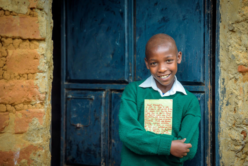 World Vision sponsored child Macharia hugs a letter that he just received from his sponsor. Travel along with a letter to a sponsored child to learn all the steps involved in getting it from your desk to the child's hands and then the child's response back to you.