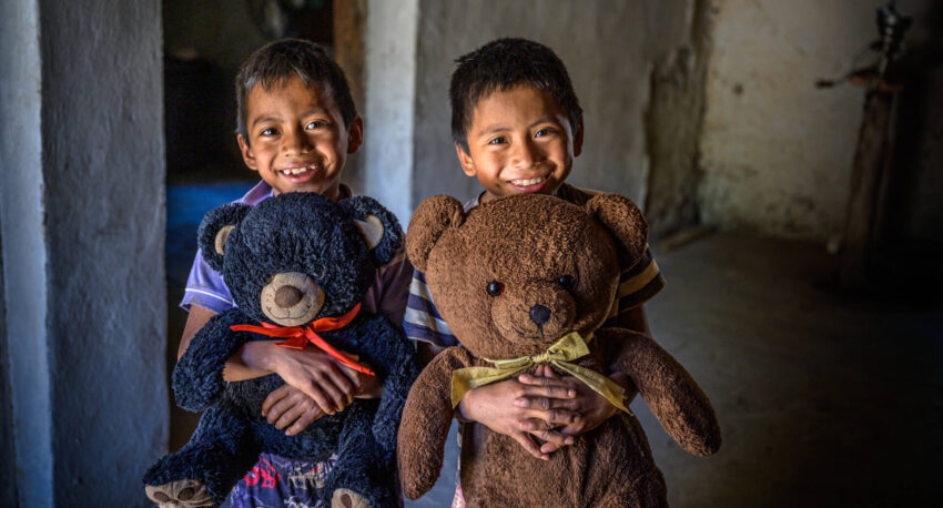 Nine-year-old twins Carlos Hernain and Carlos Joel hug their prized teddy bears, gifts from a visiting church team. The black bear is named Monkey, and the brown bear is Bear. The boys have been World Vision sponsored children for two years. (©2020 World Vision/photo by Jon Warren)