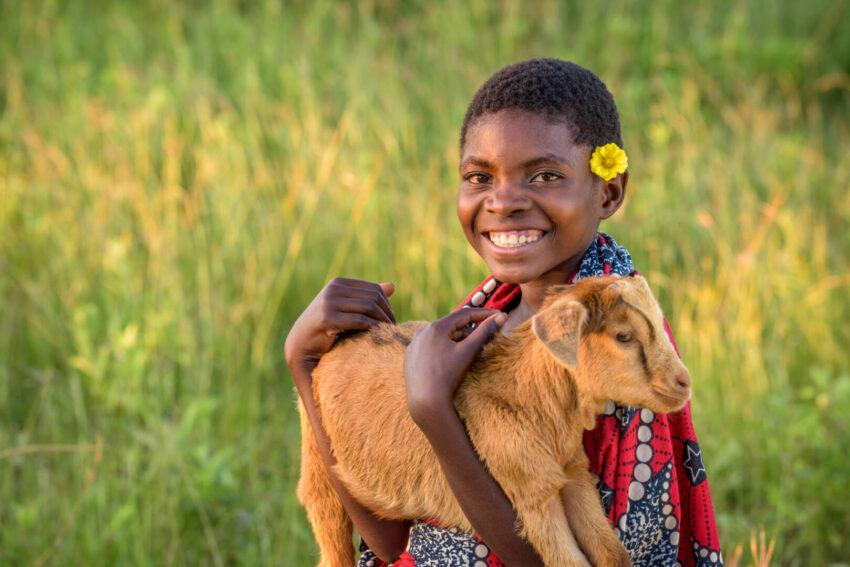 Rosemary holds one of the goats she received through the World Vision Gift Catalog. Rosemary benefited from drinking goat's milk, which provided nutritional support so she could be healthy, not hungry.