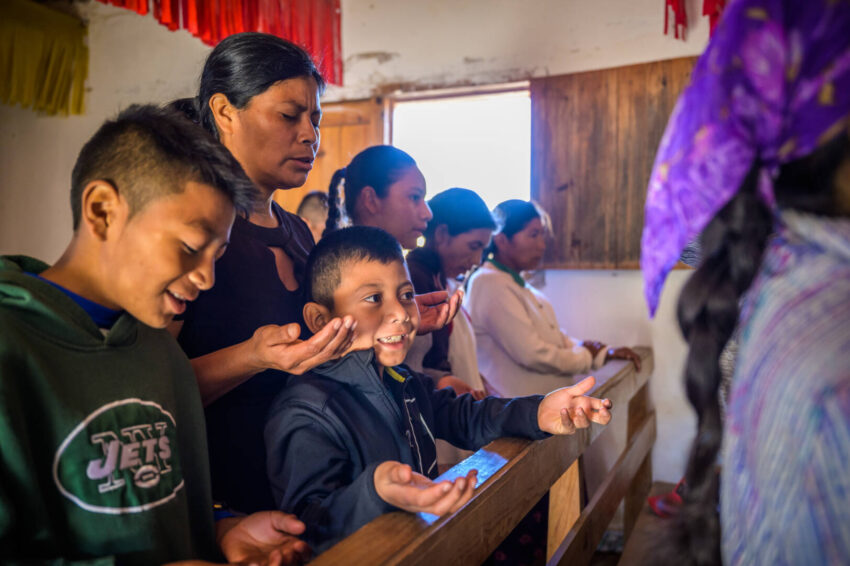 A Honduran mother and two boys pray; they're some of the people whose lives have transformed thanks to support from generous World Vision donors. You can donate on Giving Tuesday to share your blessings with people in need around the world.