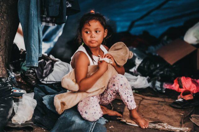 a little girl who survived Hurricane Eta sits on the street in Honduras