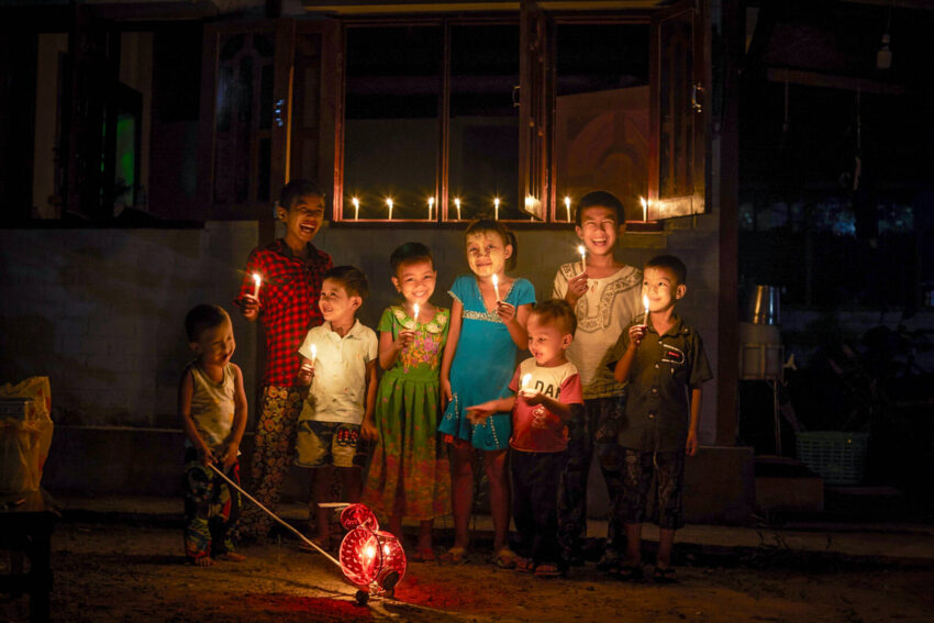 Children in Myanmar giggle together as they hold up candles for a holiday celebration.