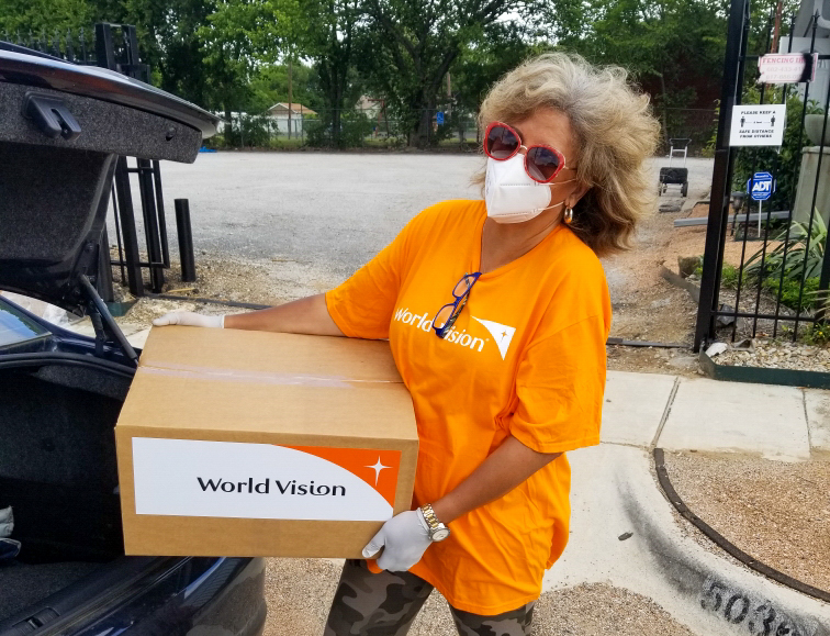 Pastor Helen Epps loads a World Vision Family Emergency Kit into a car