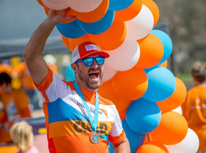 Pastor Chad McDaniel celebrates his church's participants at the 2019 Global 6K event at his church. Man in orange and blue shirt stands with one arm raised up to orange, white, and blue balloons.