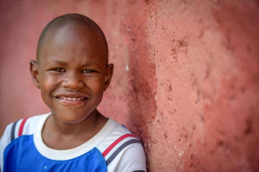 A Kenyan boy leans against a red wall and smiles at the camera.