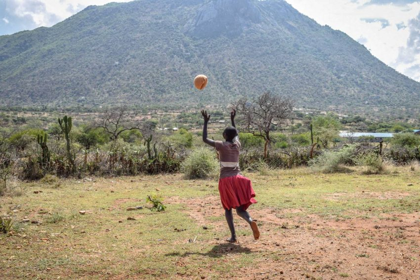 Mary plays with a ball outside the school World Vision started for children escaping child marriage and FGM. There she now attends classes and recovers from her child marriage.