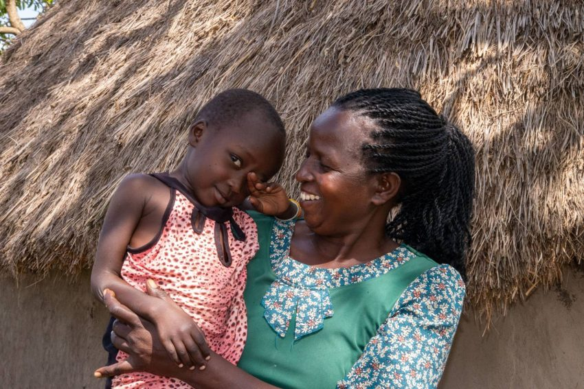 Akanya holds her granddaughter Delilah at their home in Uganda. Last year Delilah contracted malaria, and a World Vision-trained community health worker was able to diagnose her and provide anti-malarial medicine that healed her.