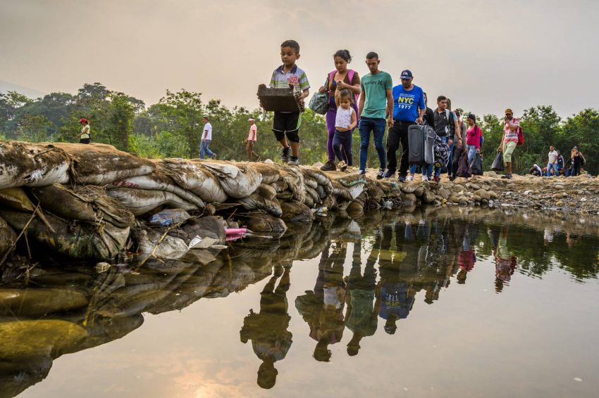 Venezuelans emerge from the woods to ford the Tachira River and cross the border illegally from Venezuela into Colombia.