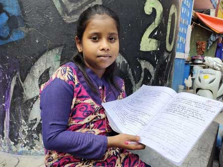 Ashmitha holds her notebook. After losing her father to COVID-19, she wants to study to be a doctor so she can save lives.
