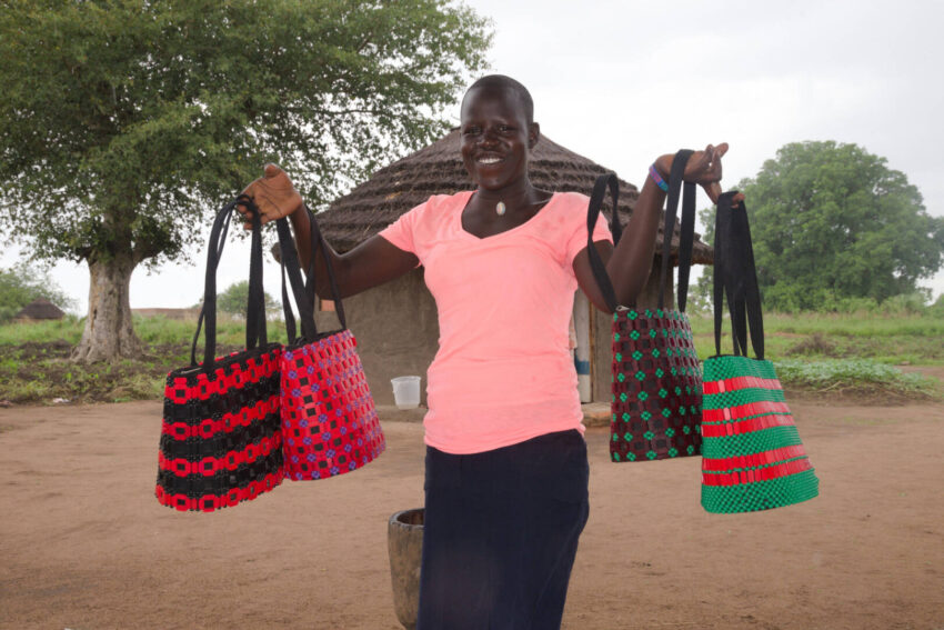 An exuberant Dominca models some of the bags that she and other women in the refugee settlement have learned to create in order to provide for their families now and in the future.