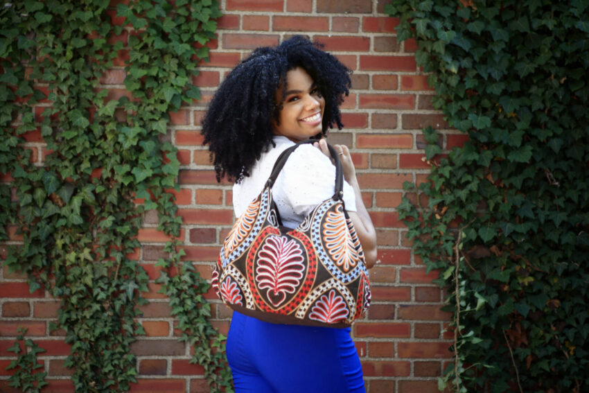A young woman in a white blouse and blue pants holds an embroidered tote bag in front of a brick wall.