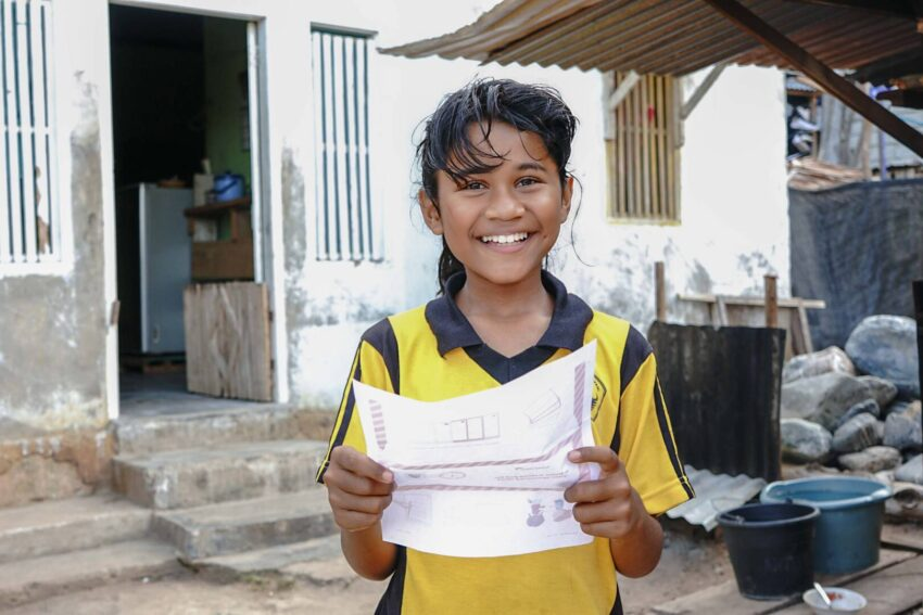 Rahmawati, 10, in Indonesia is excited to get a letter from her World Vision sponsor. A smiling girl in a yellow shirt holds a letter.
