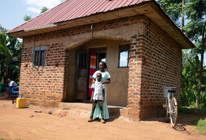 Rome, a World Vision sponsored child, and his mom, Hellen, stand in front of the new house their family was able to build in Uganda as a result of a Special Gift from his sponsor and savings Hellen accrued through her savings group.