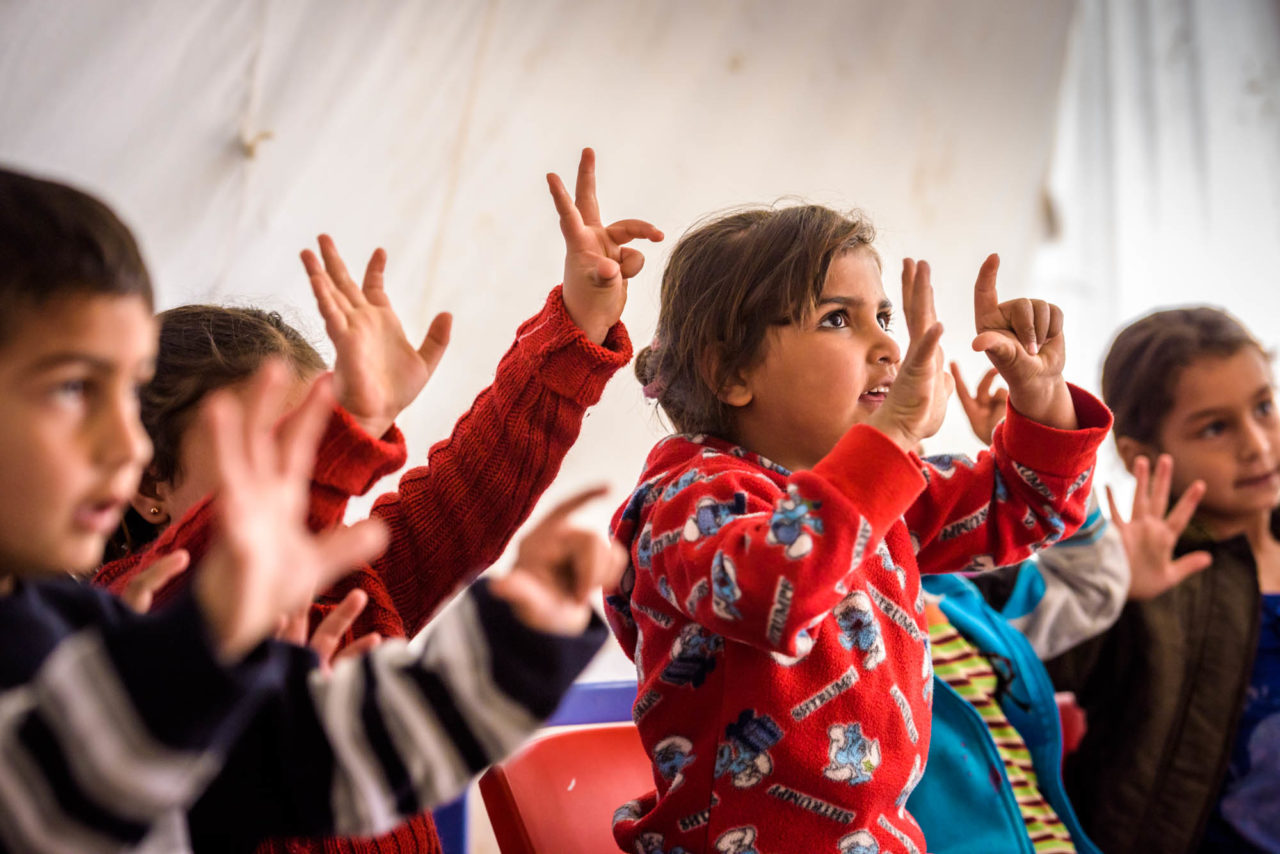Young Syrian refugee children learn to count at a refugee camp in Lebanon.