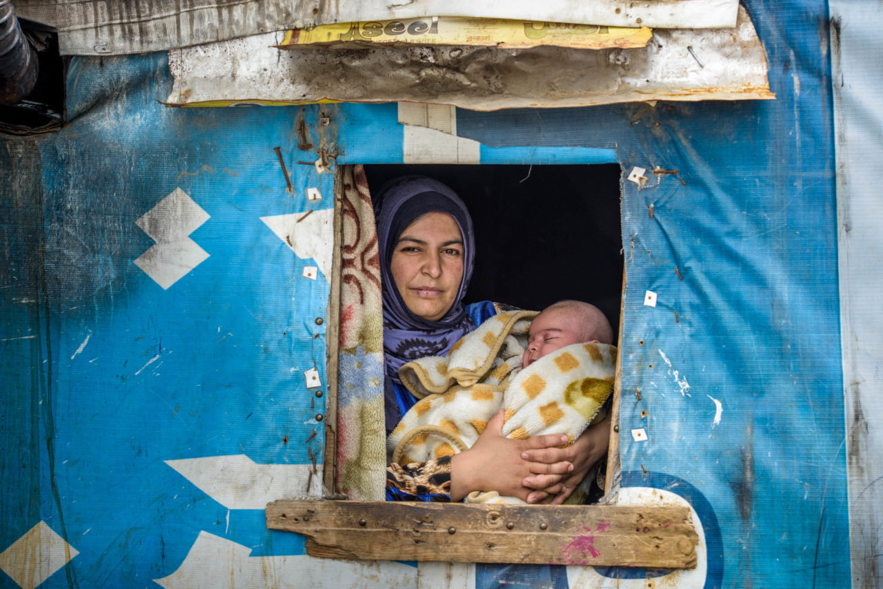 Through a tent window, we see a mother holding her 2-month-old baby boy wrapped in a heavy blanet