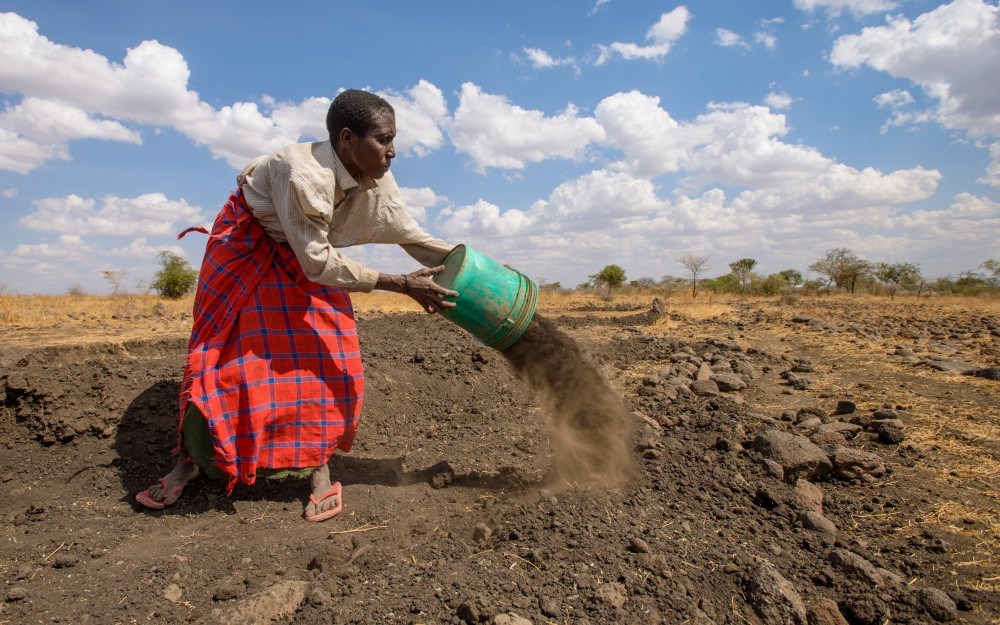 In Mbuyuni village, Tanzania, mom Neema Peter, 34, digs a water pan to collect rain to water her crops.