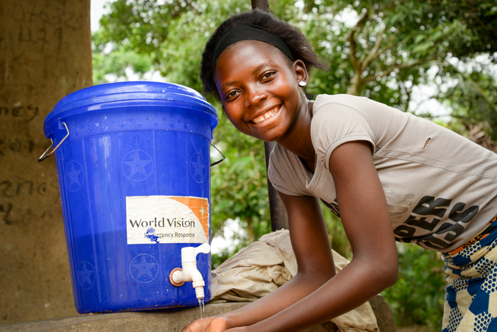 Haja Kamara, a sponsored child, washes her hands with a bucket from World Vision. She lost three of her friends to Ebola, and her walk to school is no longer exciting, she says. World Vision is thankful to God that none of its 58,000 registered children or their immediate families contracted the disease. (©2015 Jonathan Bundu/World Vision)