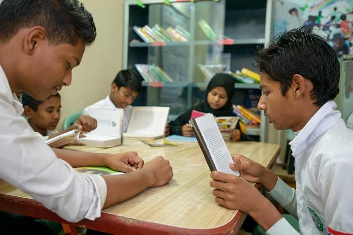 A group of children read books in the library at Dhaka Shishu Sponsorship Center in Bangladesh. PHOTO: Jon Warren/World Vision