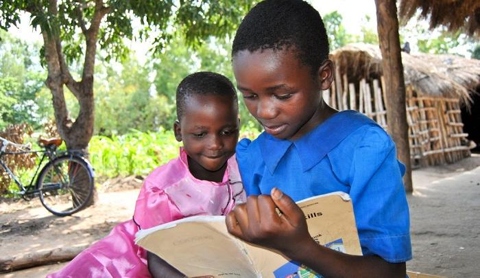Two young students in Malawi enjoy reading a book together. PHOTO: Wezzie Banda/World Vision