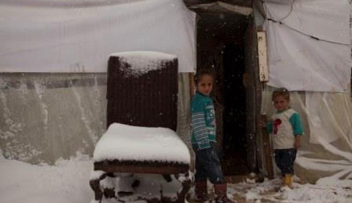 Two Syrian refugees look out from their tent in the Bekaa Valley as snow begins to cover the area.