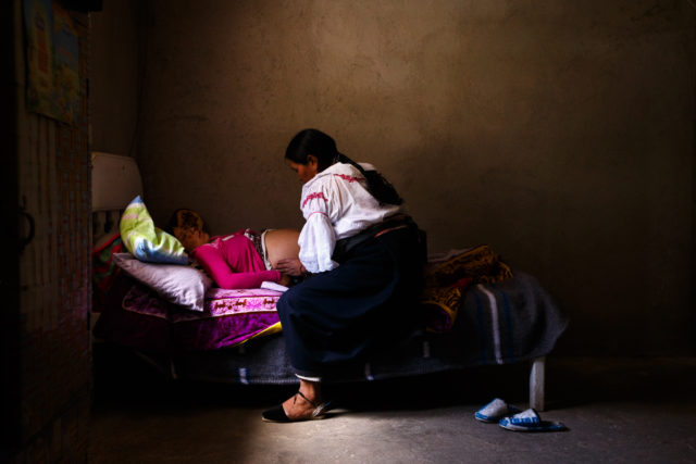 Mercedes Muenala, 53, right, gently examines Miriam Alvarez, who is 34 weeks pregnant with her second child, during a routine visit to Miriam's home July 8, near Otavalo, Ecuador.