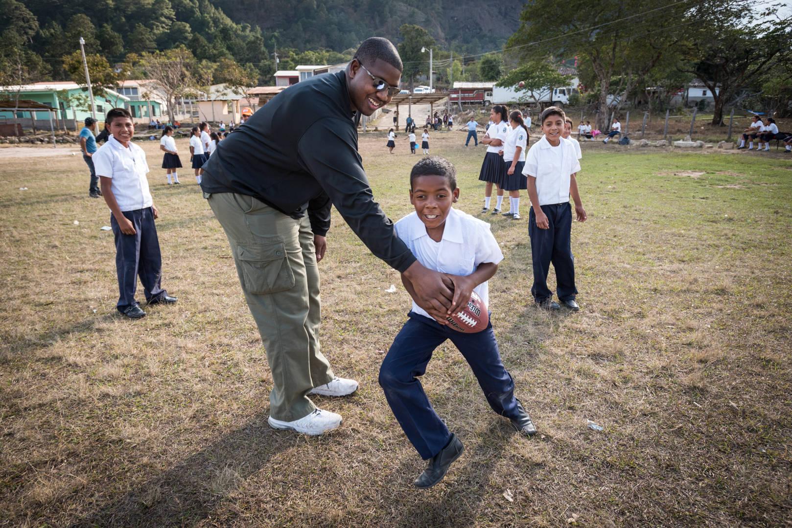NFL player Kelvin Beachum, Jr. plays American football (Fútbol Americano) with students from World Vision's Agua Blanca project and peer-to-peer tutoring program in San Juan, Honduras.