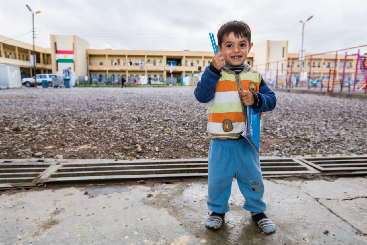 Little boy in Iraq holding pencils