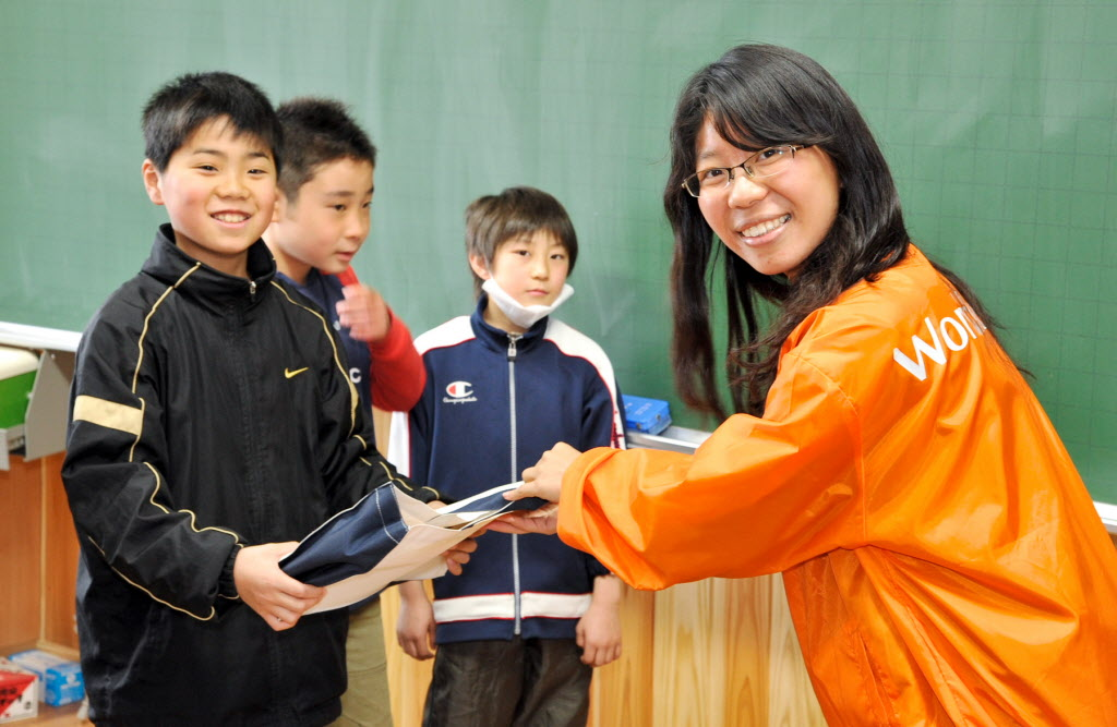 World Vision staff member distributes school supplies to students. ©2011 Itoh Kei | World Vision