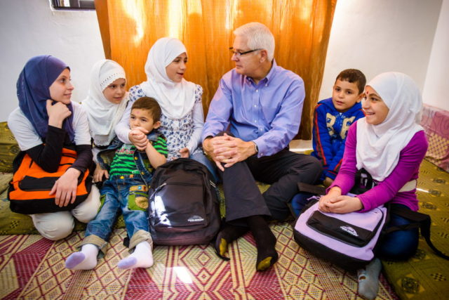Rich Stearns sitting with Syrian refugees