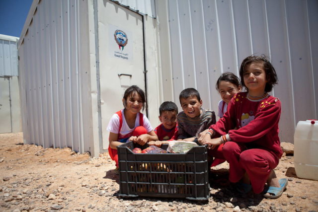 Syrian refugee children sit with a crate of food their families received while living at Azraq camp in Jordan. Syria is struggling with food production as conflict ravages infrastructure and agricultural systems. (©2014 World Vision/photo by Meg Sattler)