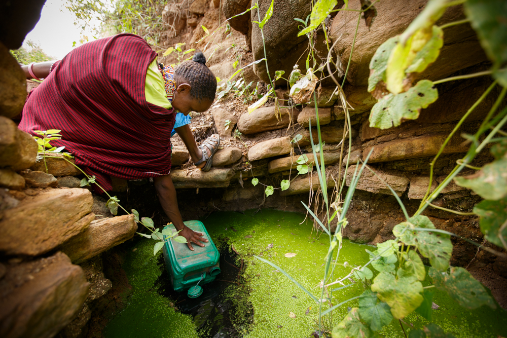 Naomi fills a jerry can with dirty water at her old water source.