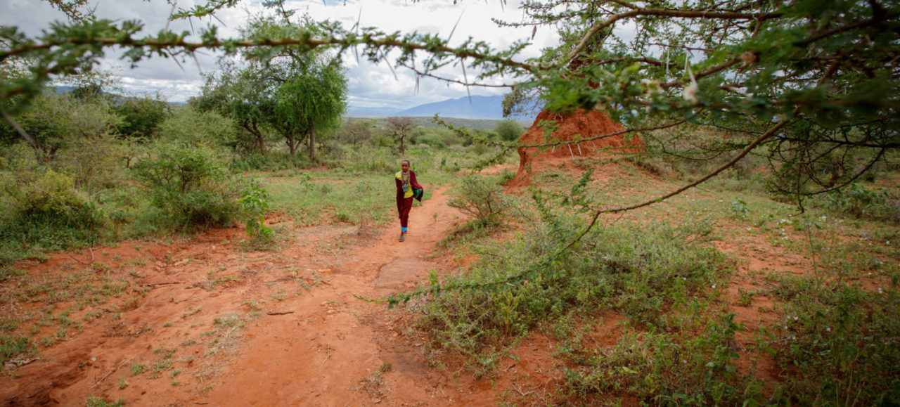 Naomi walks through the wilderness to the place she used to collect water. Now she and her family enjoy access to clean water. (©2016 World Vision, Chris Huber)
