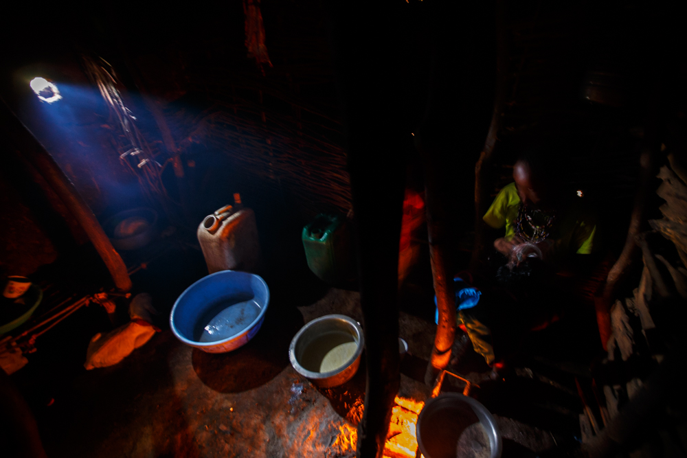 Naomi stokes the fire and washes dishes inside her house.
