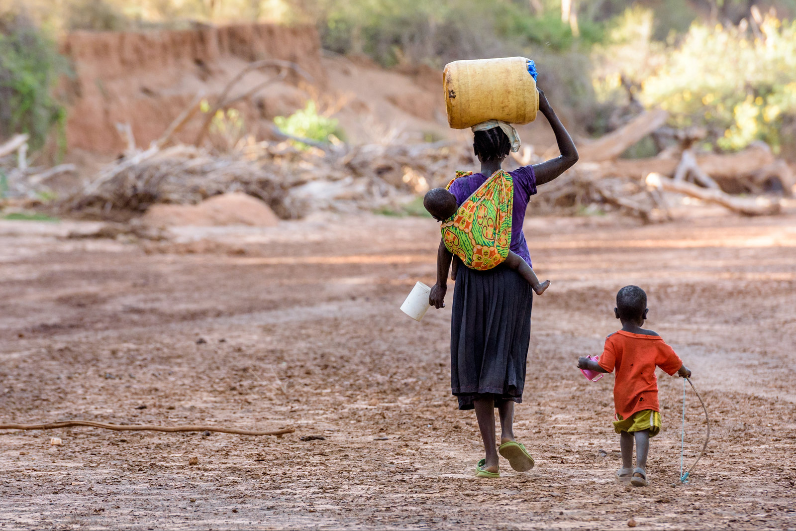 With her baby on her back and toddler by her side, Monica Lotuliapus walks in a dry riverbed in Kenya to dig for water at least twice a day, a distance of about 8K (4 miles).
