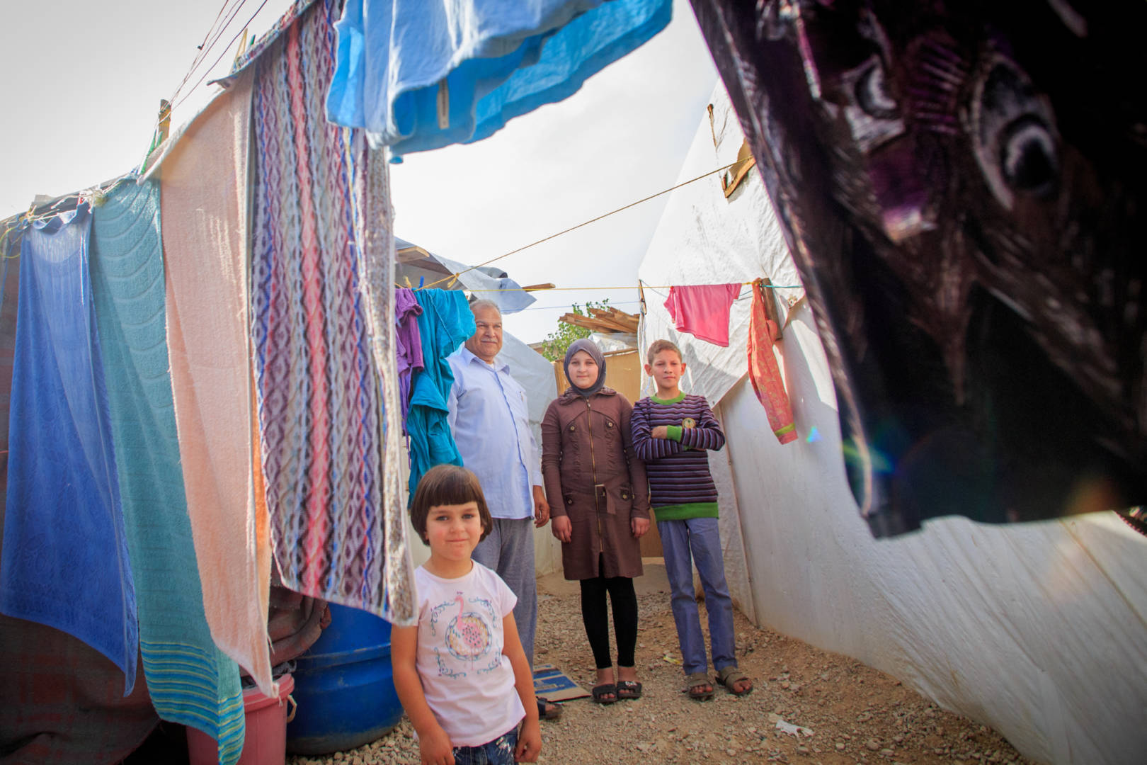 Abrar, 3, front, stands with her siblings Aya and Ammar, 13, and their father, Adnan, 60, amid laundry strung between tents in a settlement for Syrian refugees in the Bekaa Valley, Lebanon. (©2015 World Vision, Chris Huber)