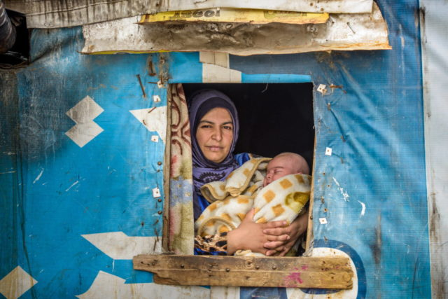 """Children of Syria. In Lebanon, Heven, a Syrian refugee, holds 2-month-old Hasan. """"I pray every day. I ask God to bring peace to Syria so we can go back and live a happy life,"""" she says. (©2016 World Vision, Jon Warren)"""