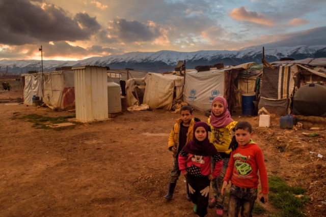 Syrian refugees gather at a makeshift camp in Lebanon. PHOTO: World Vision/Jon Warren