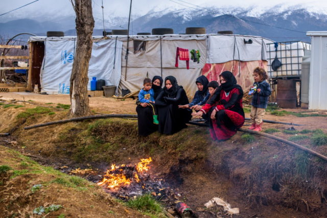 A Syrian family huddles around a fire in their informal tented settlement, located in the Bekaa Valley, Lebanon. PHOTO: World Vision/Jon Warren