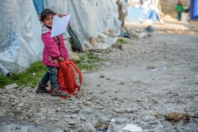 Backpack in hand, a Syrian child returns from a World Vision early education center to her family's tent in a refugee settlement in Lebanon's Bekaa Valley. (©2016 World Vision, Jon Warren)