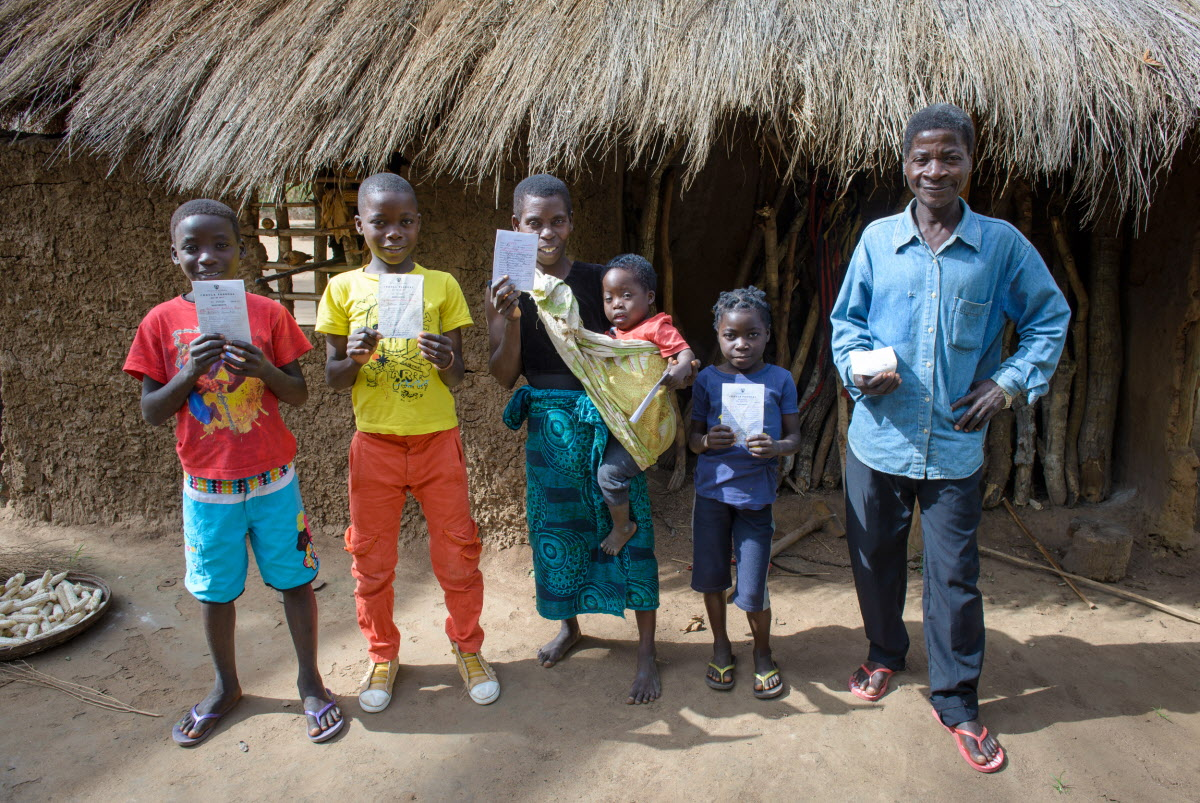 family in Mozambique holding birth registration cards