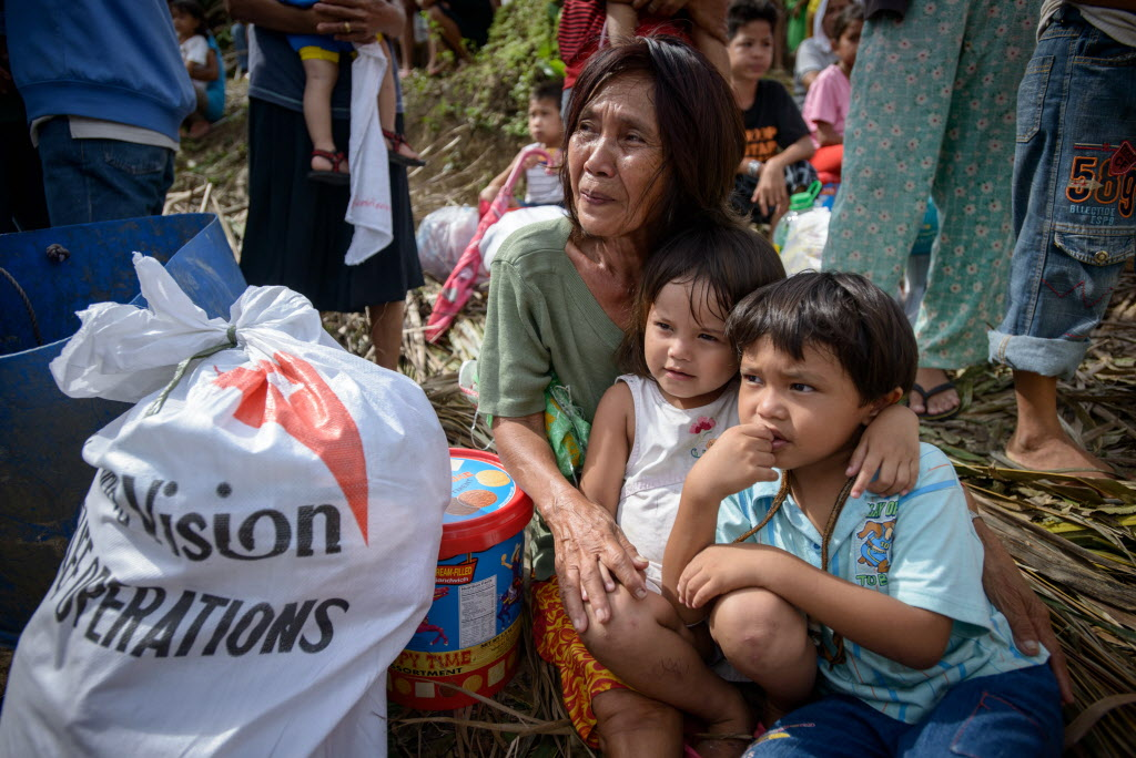 Philippines grandmother with grandchildren at relief distribution. Bag of supplies with World Vision logo.