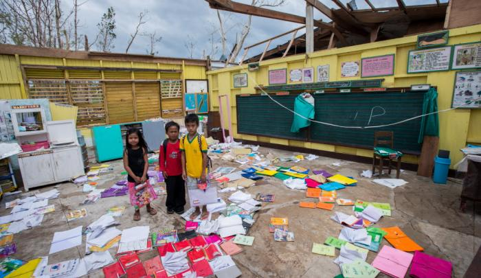 Children stand among the ruins of their classrooms