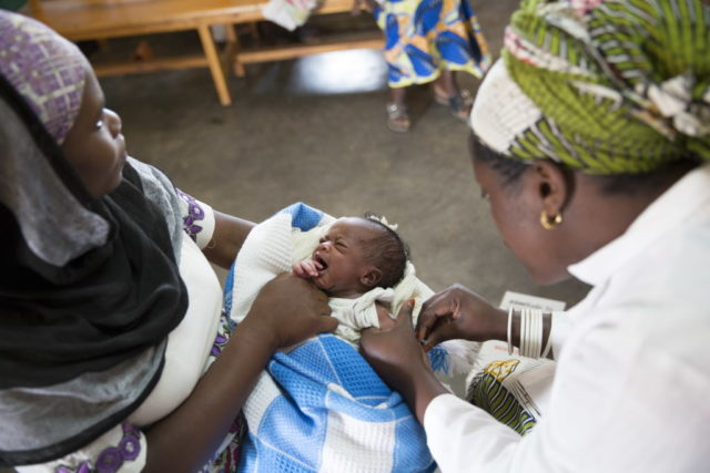 A medical staff member examines an infant at Kinihira Health Center in Rwanda. World Vision helped to provide health training and supplies for the center, which was built by the government. PHOTO: Lucy Aulich/World Vision